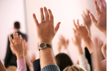 Hands raised at a business meeting