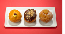 Three Bomboloni on a white plate