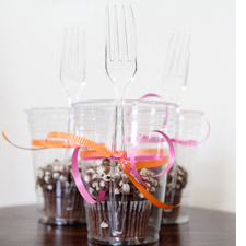 Cupcakes in clear cups with forks tied on with ribbons